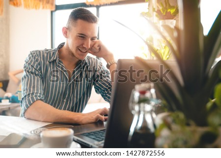 Handsome man using laptop while sitting indoors. Freelance work. place of work. New business. - Stock Image #1427872556
