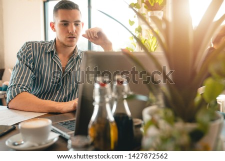 Handsome man using laptop while sitting indoors. Freelance work. place of work. New business. - Stock Image #1427872562
