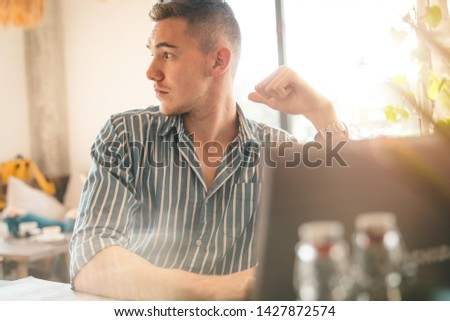 Handsome man using laptop while sitting indoors. Freelance work. place of work. New business. - Stock Image #1427872574