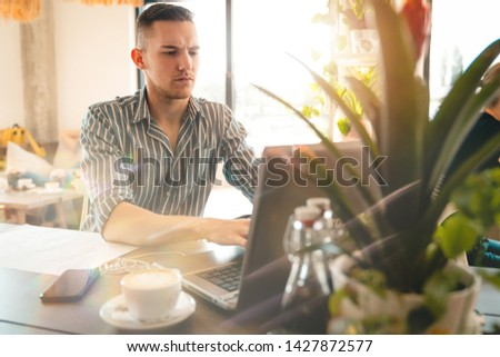 Handsome man using laptop while sitting indoors. Freelance work. place of work. New business. - Stock Image #1427872577