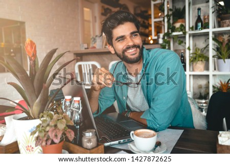 Handsome man using laptop while sitting indoors. Freelance work. Place of work. New business. - Stock Image #1427872625
