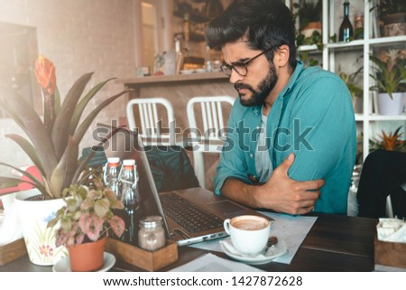 Handsome man using laptop while sitting indoors. Freelance work. Place of work. New business. - Stock Image #1427872628