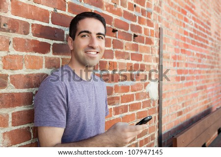 Handsome man using phone leaning on a brick wall wearing a purple t shirt - stock photo