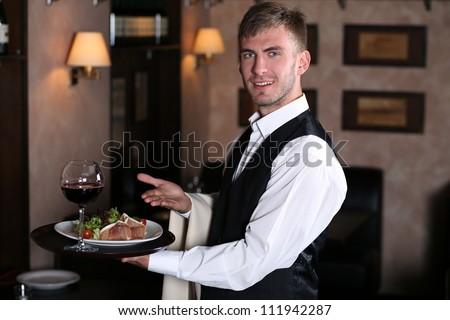 handsome man waiter in uniform at restaurant