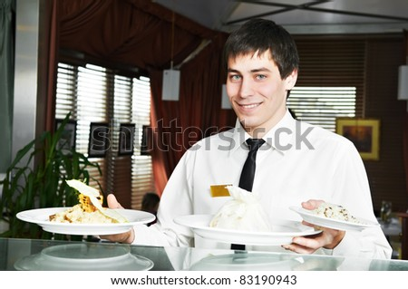 handsome man waiter in uniform with prepared food on plates at restaurant
