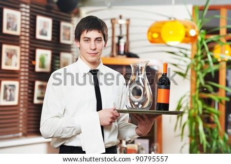 handsome man waiter in uniform with tray and wine at restaurant