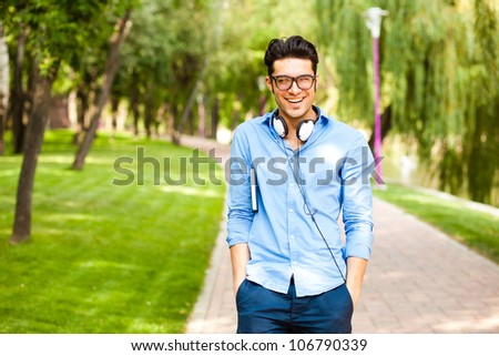 handsome man walking in the park and smiling on a sunny day