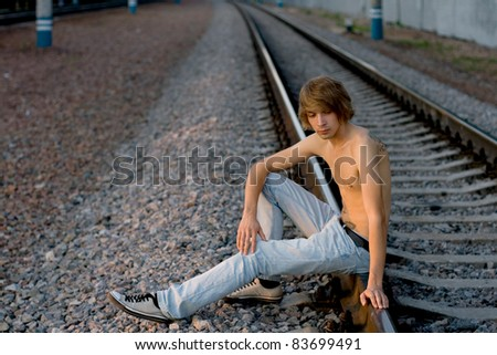 Handsome man walking near rails