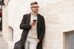 Handsome man wearing a coat walking outdoors, holding mobile phone