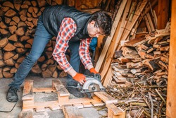 handsome man wearing a plaid shirt and a vest cuts the wood with a circular saw