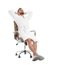Handsome man wearing bathrobe resting in chair on white background