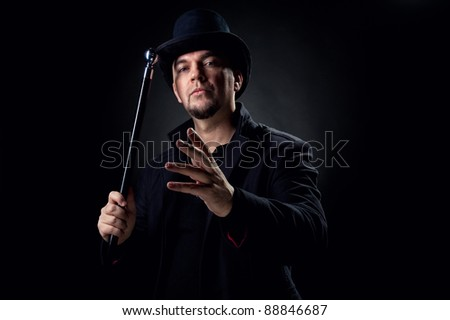 Handsome man wearing black hat and jacket holding stick over black background