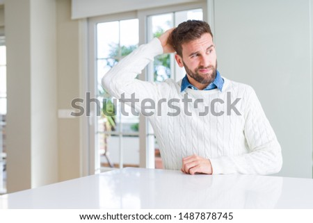 Handsome man wearing casual sweater confuse and wonder about question. Uncertain with doubt, thinking with hand on head. Pensive concept.