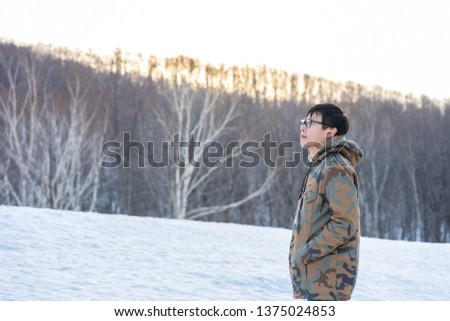 handsome man wearing cold, wearing winter clothes Among the pine trees With snow covered Feel lonely, lonely