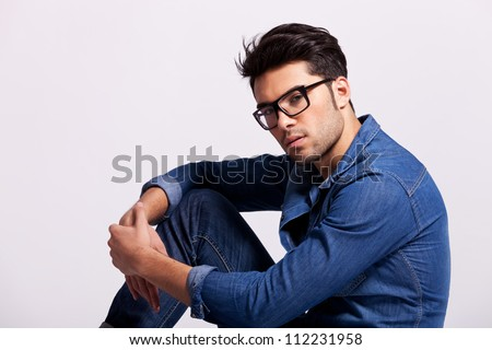 handsome man wearing glasses sitting on studio gray background and smiling at the camera