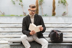Handsome man wearing jacket reading a book while sitting outdoors