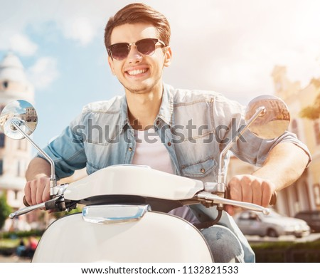 Handsome Man Wearing Sunglasses Riding on Scooter in Summer City. Front View. Happy Young Guy in Cool Glasses. Concept of Lifestyle Idea. Interesting Adventure. Best Vacation in Big Sunny City.