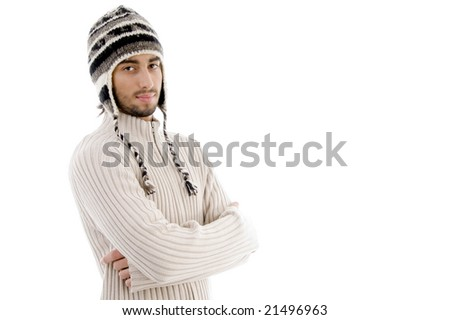 handsome man wearing woolen cap and posing with crossed arms on an isolated white background