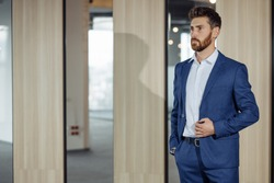 Handsome man with a red beard, wearing a blue suit, a stylish and refined man.