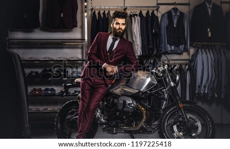 Handsome man with a stylish beard and hair dressed in vintage red suit posing near retro sports motorbike at men's clothing store. #1197225418