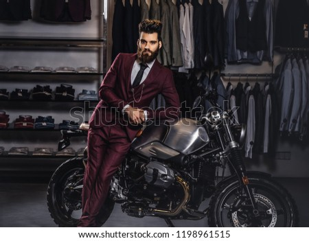 Handsome man with a stylish beard and hair dressed in vintage red suit posing near retro sports motorbike at men's clothing store. #1198961515