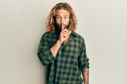 Handsome man with beard and long hair wearing casual clothes asking to be quiet with finger on lips. silence and secret concept.