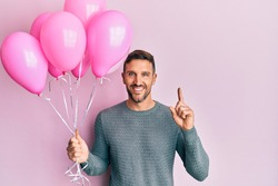 Handsome man with beard holding pink balloons surprised with an idea or question pointing finger with happy face, number one
