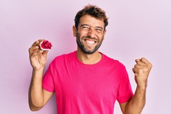 Handsome man with beard holding pink geode precious gemstone screaming proud, celebrating victory and success very excited with raised arm