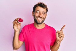 Handsome man with beard holding pink geode precious gemstone smiling happy pointing with hand and finger to the side