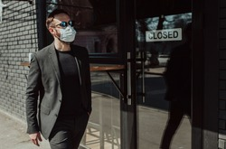 Handsome man with beard in trendy formal suit wearing a medical face mask as a precaution from viruses infection. Coronavirus - 2019.