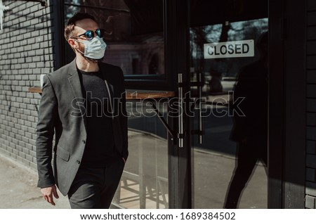 """Handsome man with beard in trendy formal suit wearing a medical face mask as a precaution from viruses infection. Coronavirus - 2019. """"Closed"""" message board on a shop window. Economic crisis"""