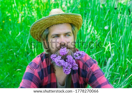 Handsome man with beard of flowers. Bearded man with decorated beard. Flowers in my beard. Portrait of handsome bearded man with flowers in his beard.