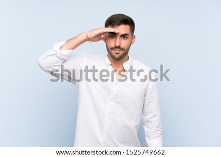 Handsome man with beard over isolated blue background looking far away with hand to look something