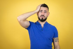 Handsome man with beard wearing blue polo shirt over yellow background putting one hand on his head smiling like he had forgotten something