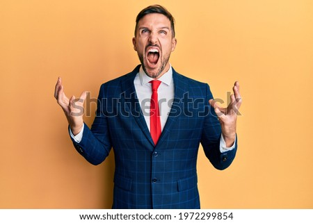 Handsome man with beard wearing business suit and tie crazy and mad shouting and yelling with aggressive expression and arms raised. frustration concept.  Stock photo ©