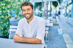 Handsome man with beard wearing casual white shirt on a sunny day smiling happy outdoors