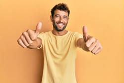Handsome man with beard wearing casual yellow tshirt over yellow background approving doing positive gesture with hand, thumbs up smiling and happy for success. winner gesture.