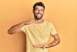 Handsome man with beard wearing casual yellow tshirt over yellow background gesturing with hands showing big and large size sign, measure symbol. smiling looking at the camera. measuring concept.
