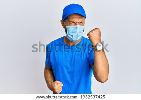 Handsome man with beard wearing courier uniform and medical mask celebrating surprised and amazed for success with arms raised and eyes closed  Photo stock ©
