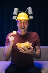 Handsome man with beer helmet on the head watching TV and eating potato chips on the couch at home. Young male sits on a sofa and eats snacks while watching a movie