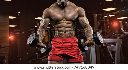 Handsome man with big muscles, posing at the camera in the gym Photo stock ©