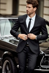 Handsome man with black car wear black suit buttoning his jacket