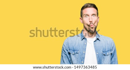 Handsome man with blue eyes and beard wearing denim jacket making fish face with lips, crazy and comical gesture. Funny expression.