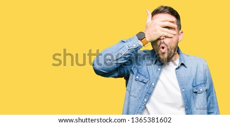 Photo of  Handsome man with blue eyes and beard wearing denim jacket peeking in shock covering face and eyes with hand, looking through fingers with embarrassed expression.