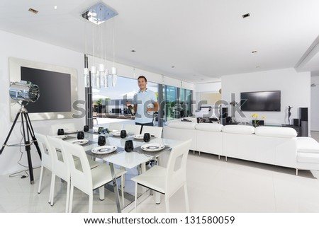 Handsome man with champagne bottle in luxury apartment