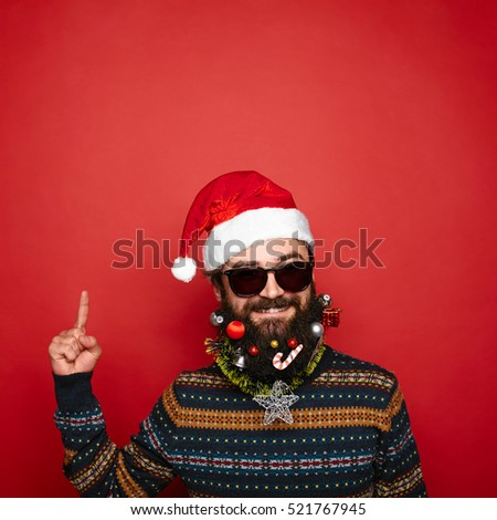 handsome man with decorated christmas beard and moustache in red santa claus hat gesturing up with his finger to copy space above his head