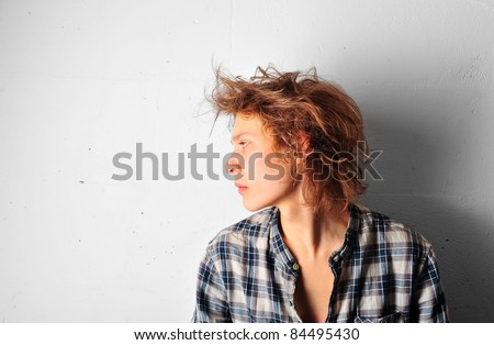 Handsome man with funky hairstyle casually leaning against the wall