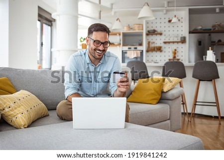 Handsome man with laptop and credit card at home, portrait. Shot of a handsome young businessman using a computer while holding a credit card in an home office