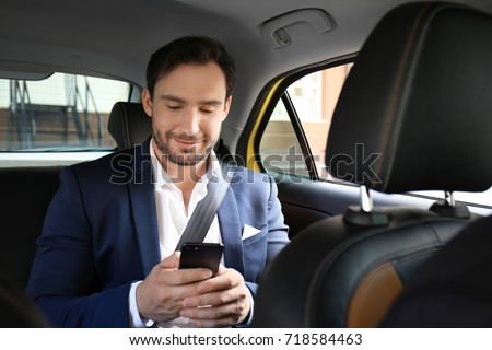 Handsome man with phone sitting in taxi car