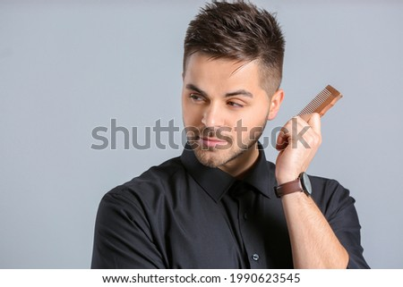 Handsome man with stylish hairdo and comb on grey background Foto stock ©